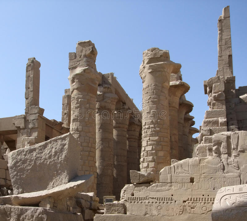 Stone remains around Precinct of Amun-Re. Sunny illuminated scenery around Precinct of Amun-Re in Egypt with various stone remains and columns in front of blue stock photo