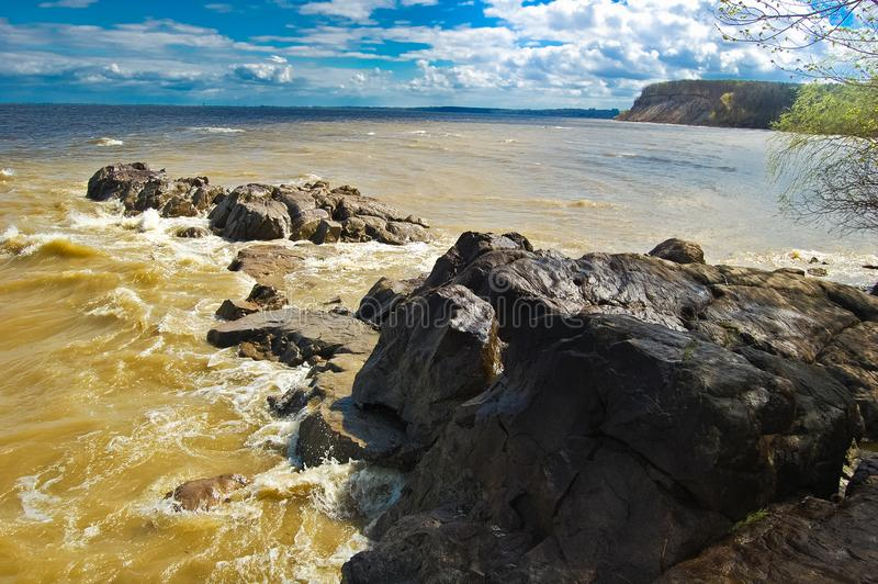 The stone ridge forms a bay of a river sandy beach. The spring fresh wind drives a wave on coast of the river Dnepr. The stone ridge forms a bay of a river sandy stock image