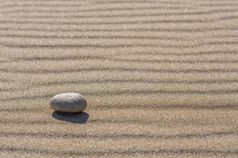 Stone on rippled sand. Minimal copy space. Nature stock photo