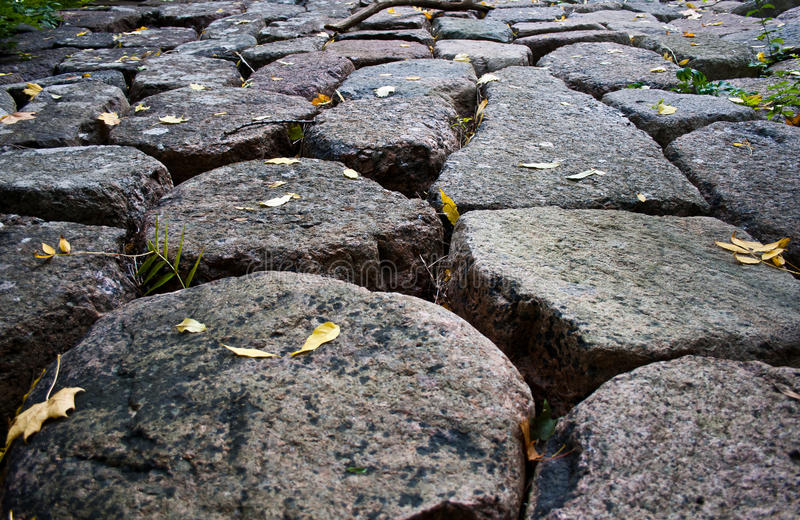 Stone road from granite cobble royalty free stock image