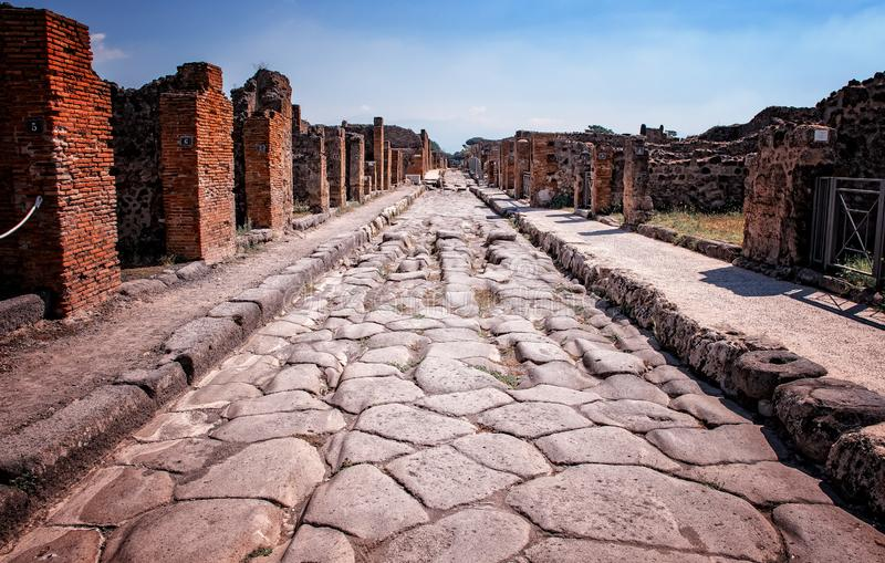 The stone road in the middle of ruins in the historical town Pompei. It is near volcano Vesuv in Italy in Europe. The city ceased to exist in 79 AD stock image