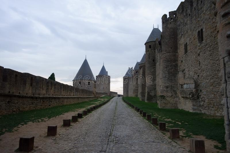The stone road between the walls and towers of the Carcassonne castle stock images