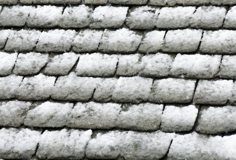 Stone roof under snow. A view of a stone roof tiles under a blanket of snow - after a snowfall royalty free stock photos