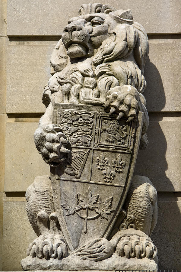 Stone Royal Lion Statue. A stone statue of a regal lion holding the heraldic shield of Canada in its paws stock images