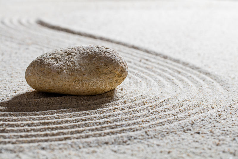 Stone on sand waves for concept of beauty spa with inner peace. Zen sand still-life - textured stone on sinuous waves for concept of beauty spa or wellness with stock images