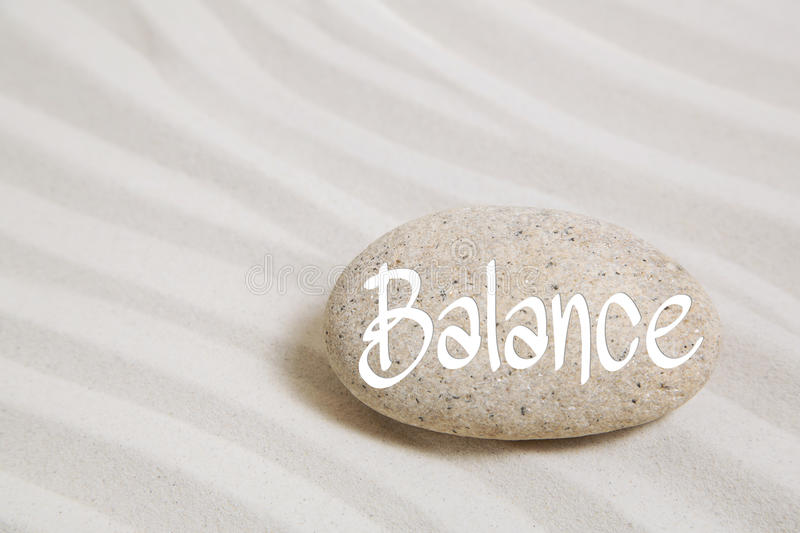 Stone in the sand with the word balance. Idea for wellness and r royalty free stock photo