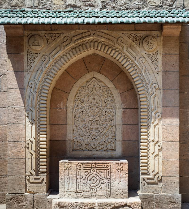 Stone sculpted drinking fountain with engraved floral decorations, Manial Palace of Prince Mohammed Ali Tewfik, Cairo, Egypt. Stone sculpted drinking fountain royalty free stock image