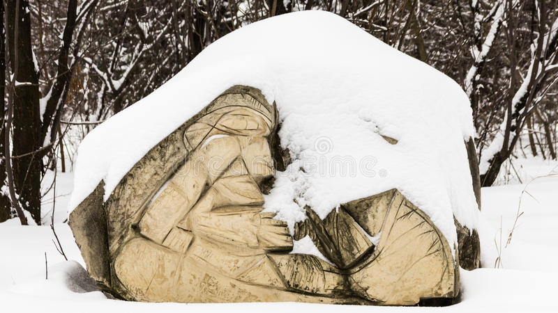 Stone sculpture covered with snow. Stone carving covered with fresh snow in park stock photos