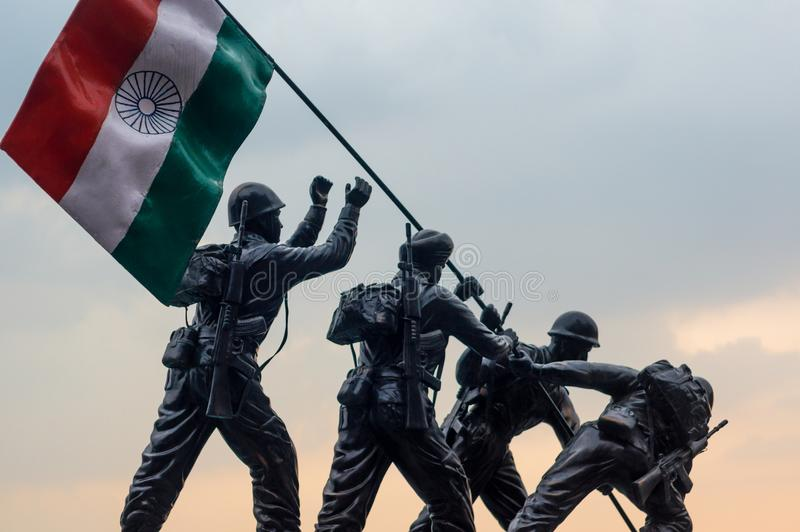 Stone sculpture of indian soldiers hoisting the indian tricolor. Shimla, India - 27th Apr 2018: Stone artwork of indian soldiers hoisting the tricolor indian stock images