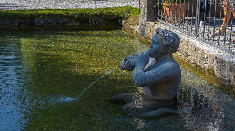 Stone sculpture in the garden of Hellbrunn Palace in Salzburg, Austria. Stone sculpture of Triton with a sea Shell Instrument in the garden of Hellbrunn Palace royalty free stock image