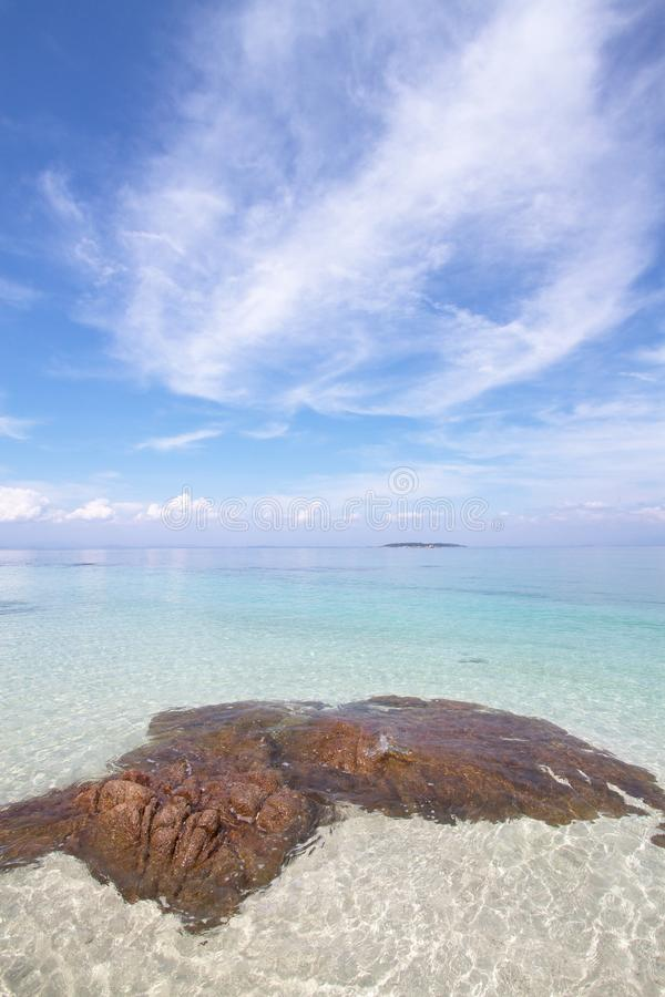 Stone in the sea. Brown stone in the sea with nice sky royalty free stock image