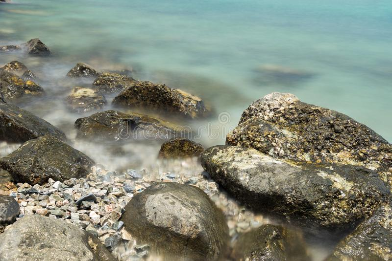 Stone in sea and wave on morning time with long exposure. The Stone in sea and wave on morning time with long exposure royalty free stock image