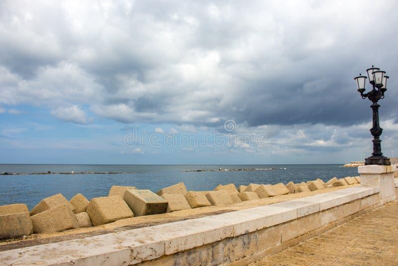Stone seaside with iron street lantern on cloudy day. Adriatic seascape. Italian panoramic coastline. Italian south background. Street decoration in Bari royalty free stock images