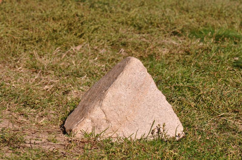 Stone pyramid. Stone in shape of a pyramid on the grass royalty free stock photos