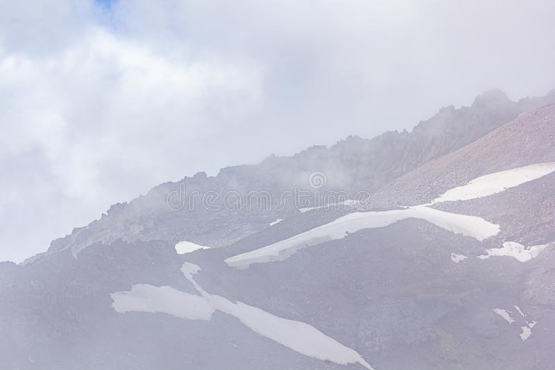 Stone and snow layers with fog create layers of mountain view in soft purples and blues. Stone trees and fog create layers of mountain view in soft purples and stock photo