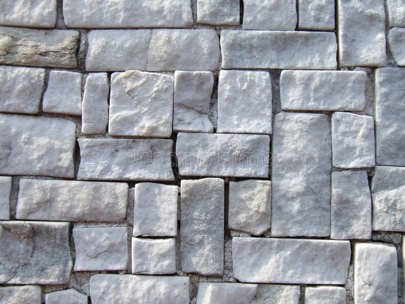 Stone square tiles. Small stone tiles in a white old wall royalty free stock photo