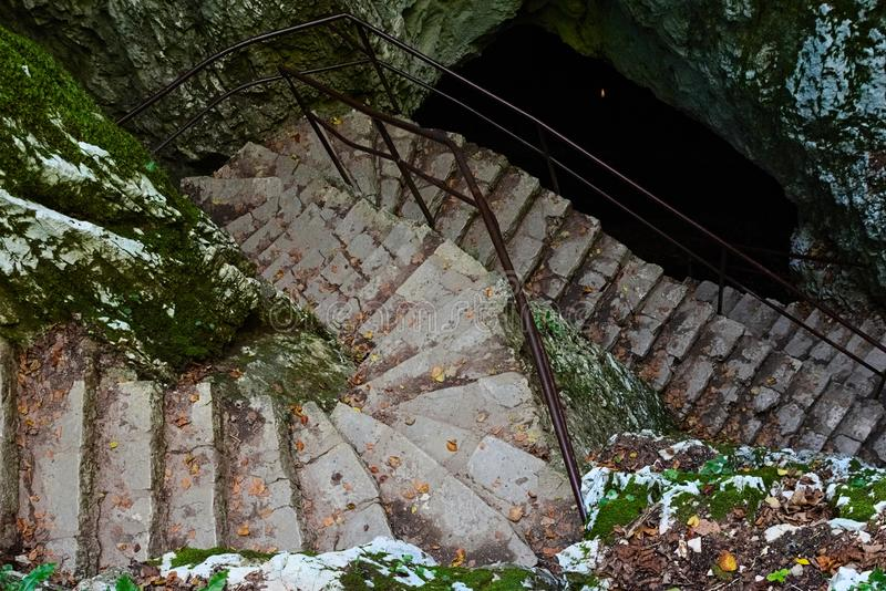 A stone staircase covered with autumn leaves that descends like a snake into a cave. A stone staircase covered with autumnal leaves fallen from the surrounding stock images