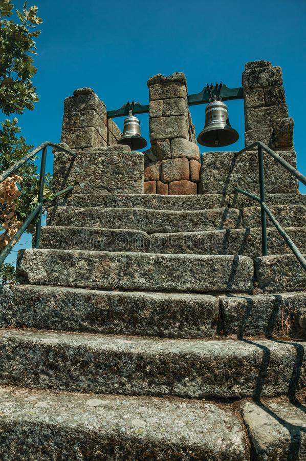 Stone staircase with iron railing and bronze bells. On top, in a sunny day at Sortelha. One of the most astonishing and well preserved medieval villages in all royalty free stock photo