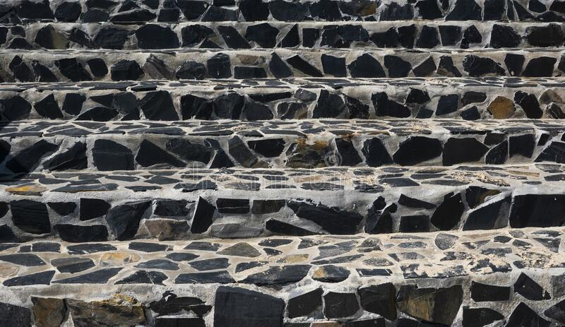 Stone stairs on the street made of black stones and gray cement. stock image