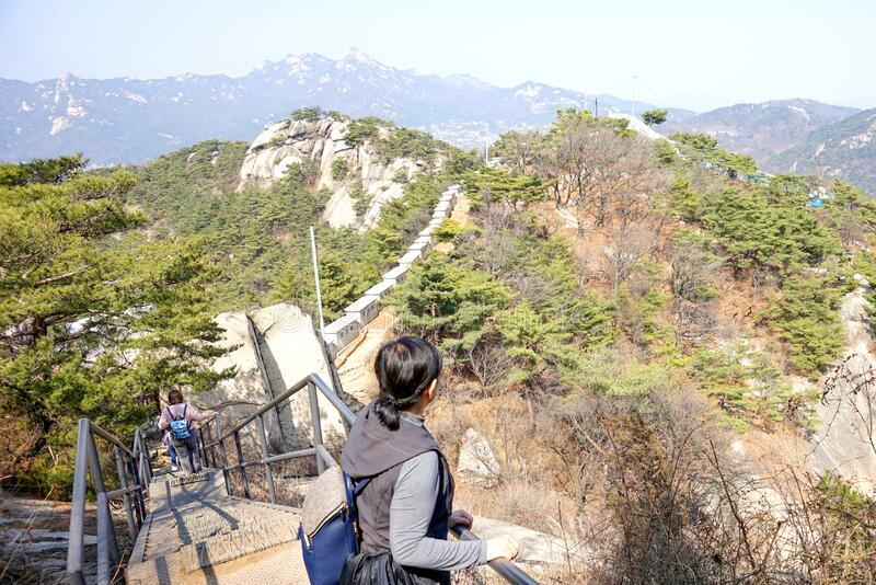 Stone stairway trail along the Seoul Fortress Wall.  Korean woman looks at the wall, forest and mountains. I stock images
