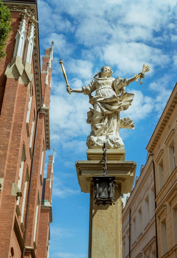 Stone statue – woman figure, holding golden arrows and scepter. Krakow/Poland- August 15, 2017: symbol of justice stone statue – woman figure royalty free stock photos