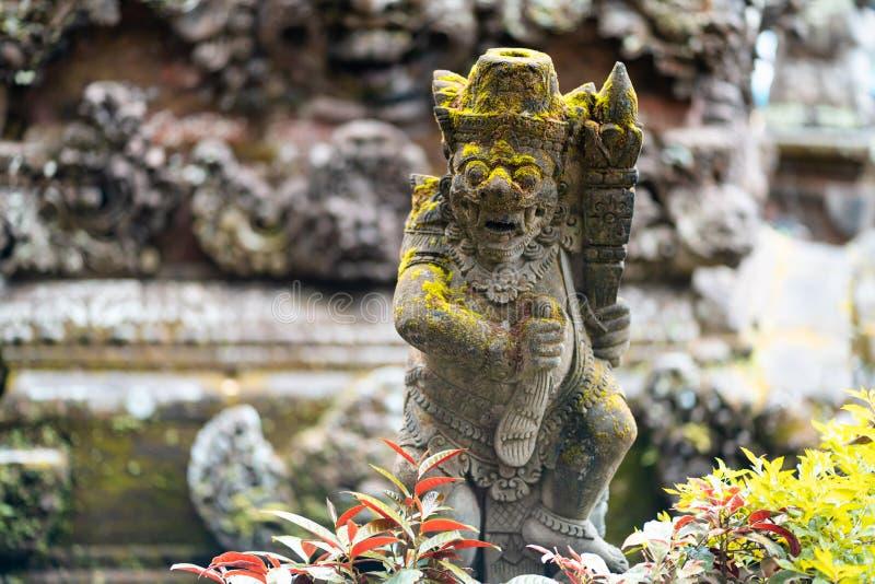 Stone statue of deity surrounded by vegetation, Bali island, Indonesia. Horizontal orientation.  stock photography