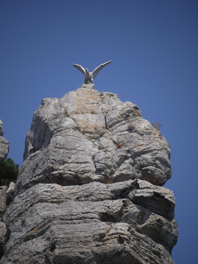 Stone statue of an eagle on a high, steep rock under the blue sky. For your design stock photos