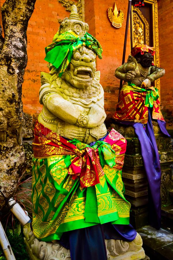 Stone statue of god guarding sacred temple with colorful traditional cloting. Monster god guarding entrance of sacred temple and royal palace in romantic Ubud stock image