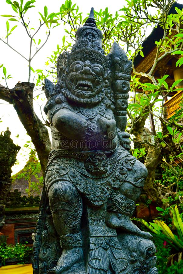 Stone statue of god guarding sacred temple with colorful traditional cloting. Monster god guarding entrance of sacred temple and royal palace in romantic Ubud stock photos