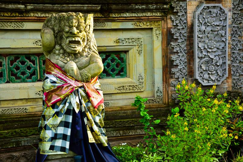 Stone statue of god guarding sacred temple with colorful traditional cloting. Monster god guarding entrance of sacred temple and royal palace in romantic Ubud royalty free stock photos