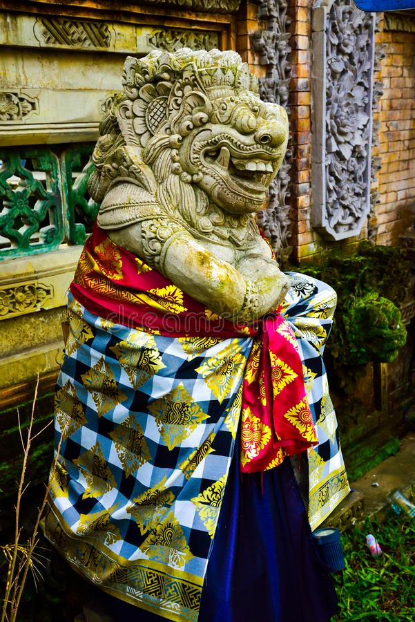 Stone statue of god guarding sacred temple with colorful traditional cloting. Monster god guarding entrance of sacred temple and royal palace in romantic Ubud royalty free stock image