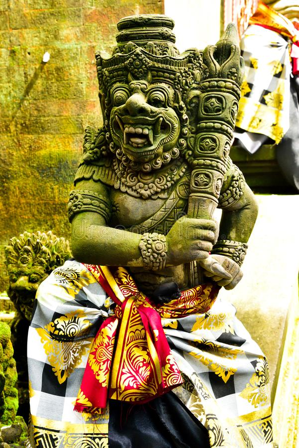 Stone statue of god guarding sacred temple with colorful traditional cloting. Monster god guarding entrance of sacred temple and royal palace in romantic Ubud stock photography