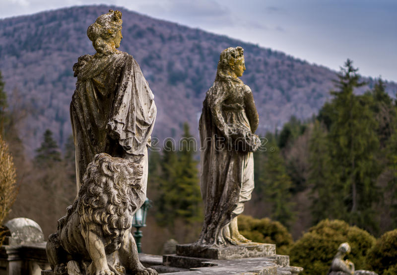 Stone statues and a stone lion in a public garden royalty free stock photography