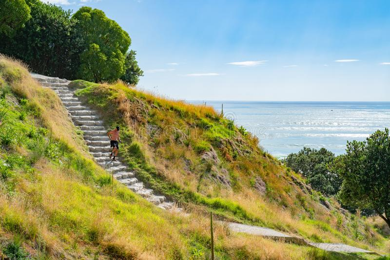 Stone steps down track up Mount Maunganui with view beyond to Pacific Ocean. TAURANGA NEW ZEALAND FEBRUARY 12 2019; Male jogging down stone steps down track up royalty free stock photo