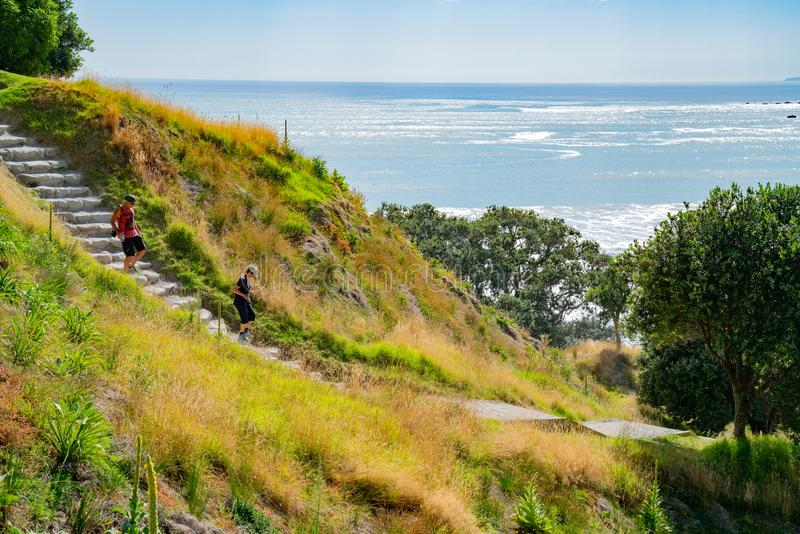 Stone steps down track up Mount Maunganui with view beyond to Pacific Ocean. TAURANGA NEW ZEALAND FEBRUARY 12 2019; People on stone steps down track up Mount stock images