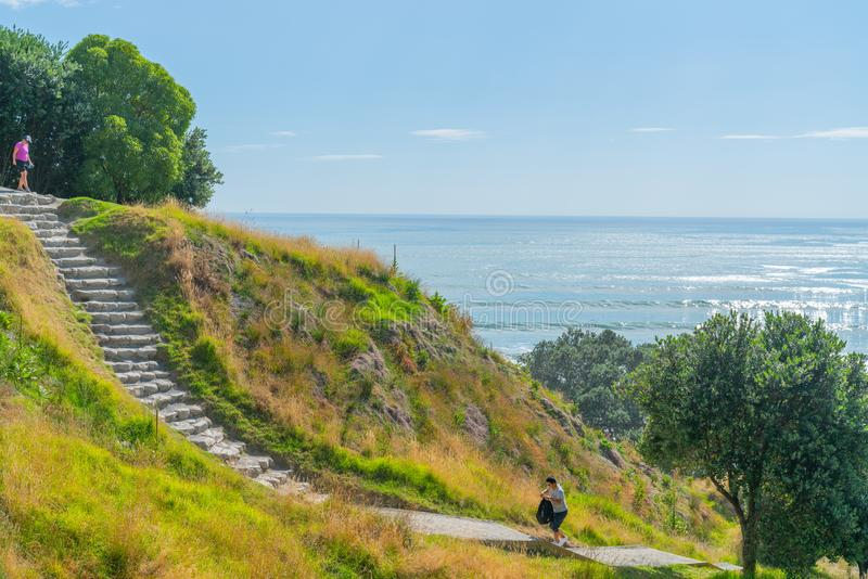 Stone steps down track up Mount Maunganui with view beyond to Pacific Ocean. TAURANGA NEW ZEALAND FEBRUARY 12 2019; Stone steps down track up Mount Maunganui stock photo