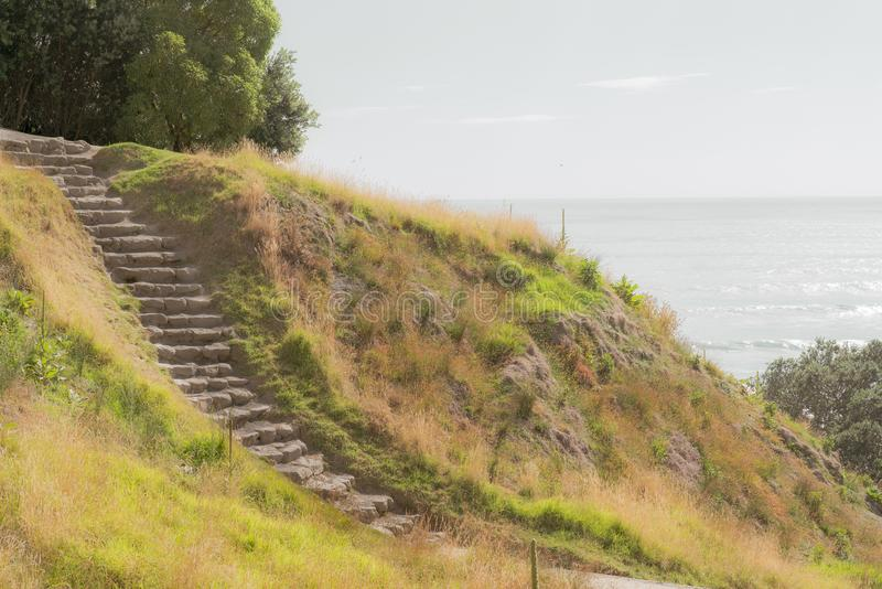 Stone steps down track up Mount Maunganui with view beyond to Pacific Ocean. Vintage effect stone steps down track up Mount Maunganui with view beyond to Pacific royalty free stock photo