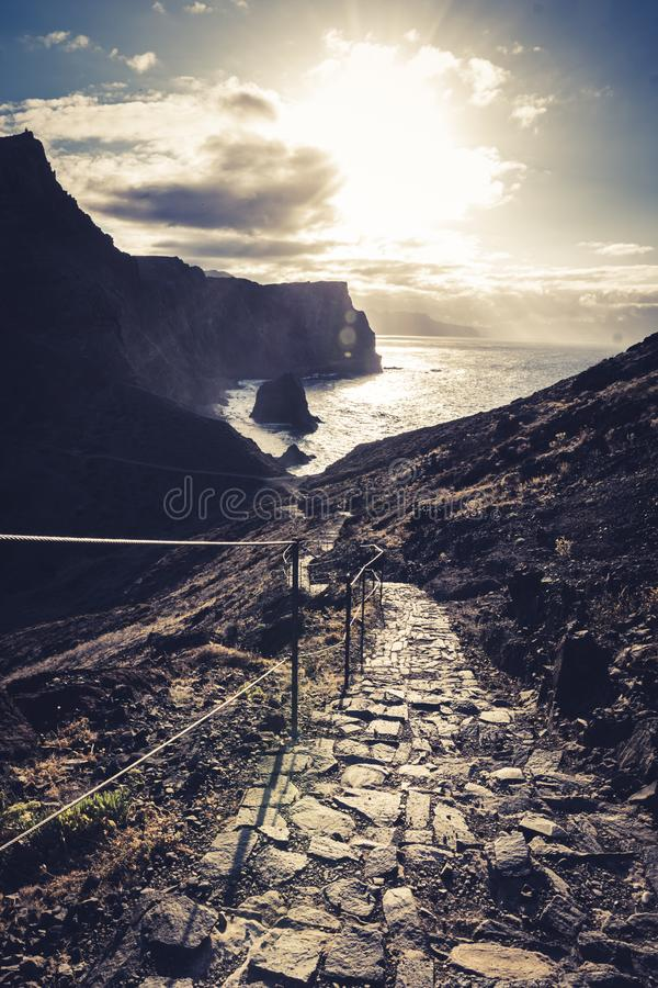Stone steps in a rough rocky cliff landscape on a hiking trail going Down to the sea during sunset royalty free stock photo