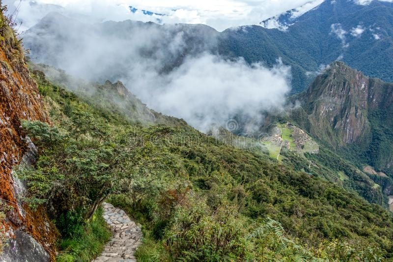 Stone steps on the steep slope of Machu Piccu Mountain with view on the Machu Picchu Inca citadel. Located on a mountain ridge above the Sacred Valley royalty free stock photos