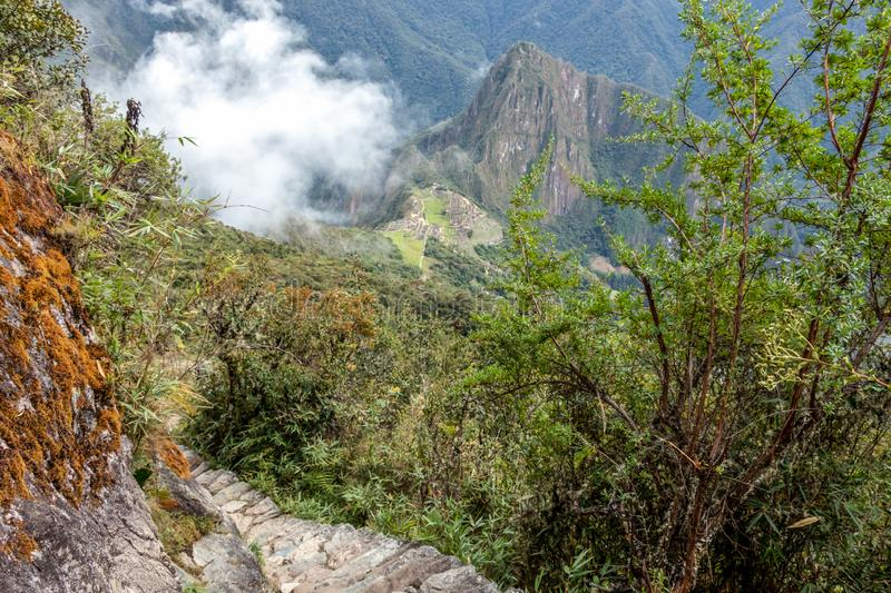 Stone steps on the steep slope of Machu Piccu Mountain with view on the Machu Picchu Inca citadel. Located on a mountain ridge above the Sacred Valley stock images