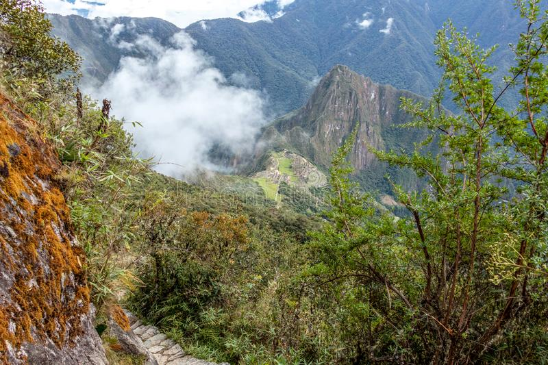 Stone steps on the steep slope of Machu Piccu Mountain with view on the Machu Picchu Inca citadel. Located on a mountain ridge above the Sacred Valley royalty free stock photo