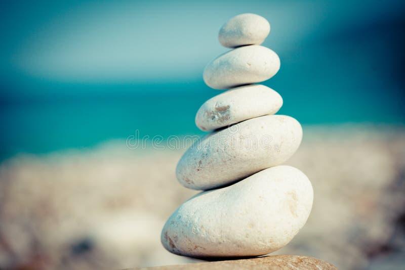 Stone stupa at the sea coast. White stones piramidic under blue sky royalty free stock photography