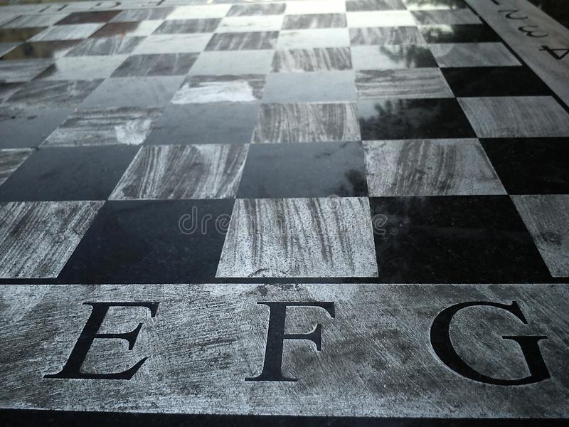 Stone table with a chessboard. Black and white chess fields. The letters E, F and G. Reflection of light on a polished surface. royalty free stock image