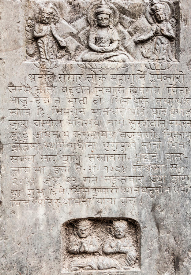 A stone tablet. An ancient Buddhist text in Sanskrit etched into a stone tablet stock photos