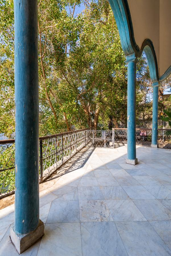 Stone terrace with metal fence against green trees royalty free stock photo
