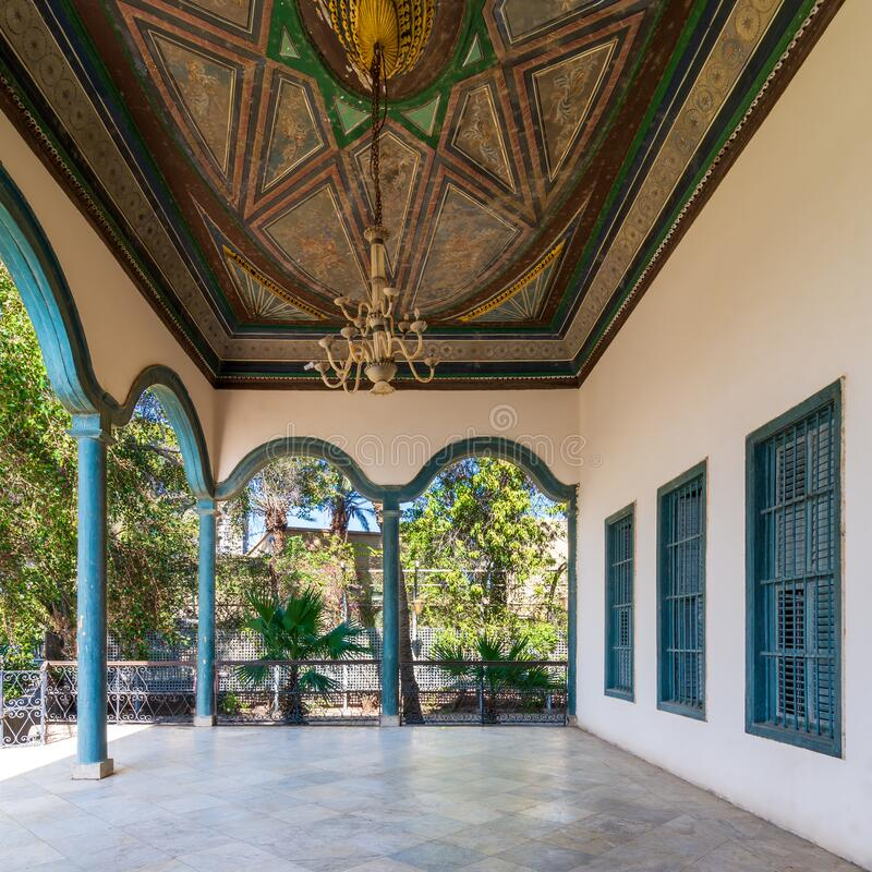 Stone terrace with metal fence, decorated painted ceiling and green columns against green trees stock photos