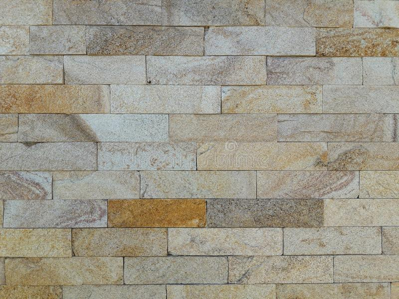 Stone texture. Finishing the facade of the house.Gray, brown and yellow color background stock photos