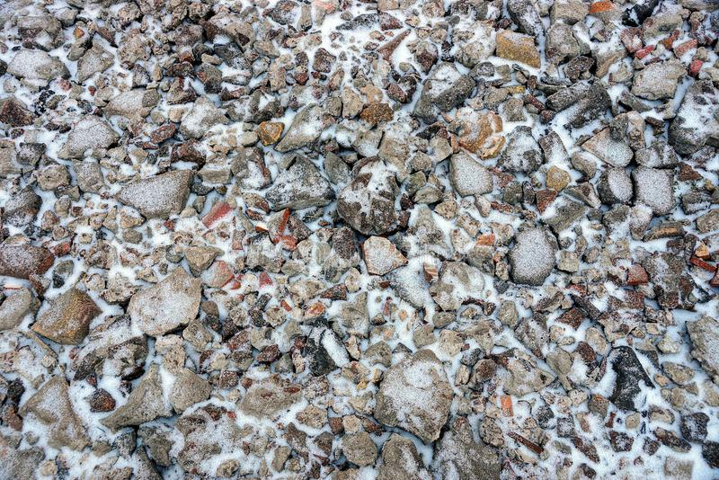 Garbage from stones and bricks in a heap under snow. Stone texture of garbage from stones and bricks in a pile under snow royalty free stock photography