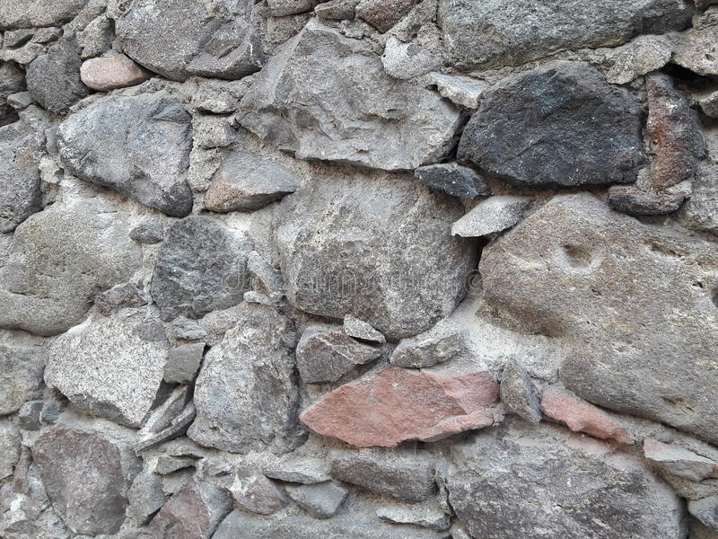 Stone Textured Background of Old Handcrafted Wall with Gray, Pink, Black Colored Rocks Laid in Rustic Mexican Architectural Style stock photos