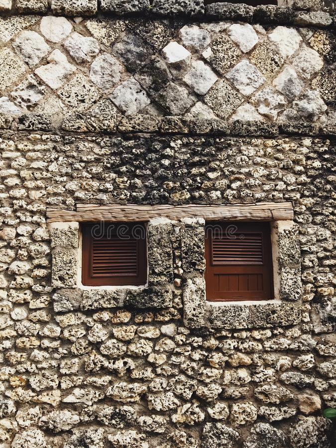 Stone textured wall of house in Altos de Chavon. Background photo of antique-like wall made of light stone with two small windows with no glass. Stones have royalty free stock images